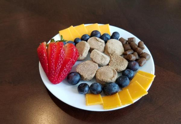 A plate of dog treats includes strawberry slices, blueberries, cheese, training treats, and a few freezes-dry dog treats.